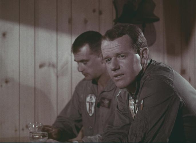 A man in a flight suit sits at a bar. Another man sits beside him. The wall behind them is wood paneling.
