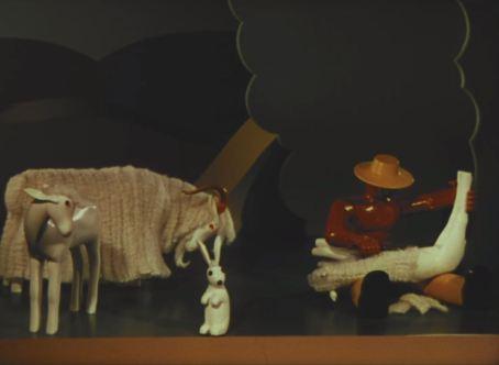 A carved figure shears a sheep.