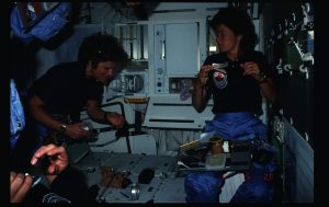 View of 41G Mission Specialist 2 (MS2) Sally K. Ride, and MS1 Kathryn D. Sullivan, eating in the Middeck (MDDK) during 41G. Flight dates were October 5-13, 1984. 255-STS-41G-02-032
