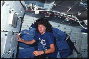 On middeck, Mission Specialist (MS) Ride steadies herself in front of forward locker MF71E. Meal tray assembly (ASSY) and control panel MO58F appear overhead and sleep restraints are visible on starboard wall. 255-STS-s07-13-578