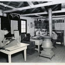 """35-GE-1E-34-544 """"Leo's Studio, Spokane, Wash. 34-544 Educational Buildings of the CCC house more materials and are used more than most other buildings. Co. 2503's Educational Adviser, Allen, seated center, was beginning to move into a new Educational Building size 20 x 80 adjacent to preset building August 26. Typical Educational Facilities in Fort Missoula District Montana consists of two 20 x 80 ft. buildings given over to use of Enrollees for Education and Recreation."""""""