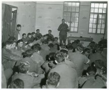 """111-SC-200477 """"U.S. Airborne men attend Christmas service in Bastogne while the city was under siege. Many of the men here are wounded, but could not be evacuated."""" Photo taken 12/25/1944"""