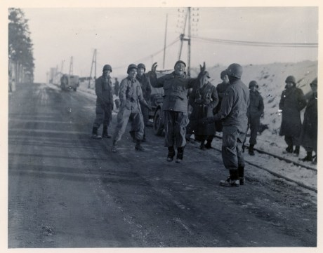 """111-SC-253857 """"Troops of the 101st Airborne Division holding Bastogne against the Germans laugh as they watch a comrade pretend to jump rope to keep warm. They are waiting here for supply planes to drop much needed medical supplies and ammunition by parachute."""" Photo taken 12/25/1944"""