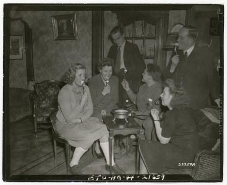 """111-SC-323598 """"This Belgian family is introduced to the American custom of toasting marshmallows. Cpl. Wally J. Branson of Chicago, IL is their guest on Christmas Eve. Namur, Belgium."""" Photo taken 12/24/1944"""