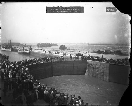 """Crowds of people standing on each side of the new lock, as well as on the lock gates which are closed. Label on original photograph reads, """"August 3, 1896. Opening of Poe Lock. At intermediate gate."""""""
