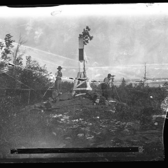77-SOO-U-11: Resurvey of St. Marys River: Men Surveying At Unidentified Location, Possibly Bare Rock Station? [At some point in the past, the broken glass support was repaired with tape, distorting the image.]
