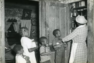 """""""Negro woman tenant storing her canned food in a pantry built on back porch, with the help of her grandchildren. Allendale County, South Carolina. September 1940."""" (Image ID: 16-G-162-S-7146)"""