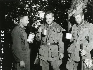"""111-SC-324432 """"Pvt. John C Rodrigues, Pawtuckett, R.I., gives two weary paratroopers their first taste of GI food in 37 days. They were captured by the Germans the latter part of D-Day, escaped after several days imprisonment during a night march , living off raw potatoes most of the time. They contacted US forces on July 15th 1944. Left to right: Sgt. Robert D. Henderson, Seattle, WA, and Sgt. Havrill W. Lazenby, Nashville, TN. 505th Parachute Regiment, 82nd Airborne Division."""" July 17th 1944."""