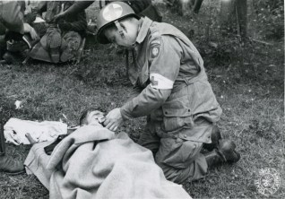 """111-SC-190228-S """"An American Medical Officer , who went to France with an Airborne Division, (82nd), lights a cigarette for a wounded American whose landing was less successful than that of the officer. St. Mere Eglise, France. 82nd Airborne Div."""" June 12th 1944."""