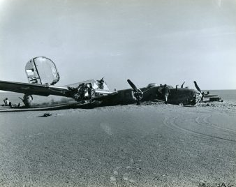 An external view of the abandoned B-24 which, according to investigators, bellied into the sand with three engines feathered and without fuel; the fourth engine was still operable. Wheel tracks on the sand are of the geological team that discovered the wreck. Local ID: 342-B-ND-075-4-162171AC