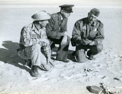 James W. Backhaus, William G. Woods, and Col. Stebbins Griffith. In the foreground is a US military canteen. Local ID: Local ID: 342-B-ND-075-4-92671AC