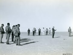 """A prayer service at the location of the bodies of the """"Lady Be Good"""" crew members in the Libyan Desert provided a simple but solemn commemoration. Chaplain (Lt. Col.) William G. Woods, Chief of Wheelus Chaplains, conducts the service while members of the US Air Force investigating part and oil exploration personnel listen in silence. Local ID: 342-B-ND-075-4-92672AC"""