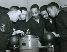 CQM L.J. Russell instructs sailors. Left to right: Charles W. Divers, Royal H. Gooden, Calvin Bell, and Lewis F. Blanton (Local ID: 80-G-214542)