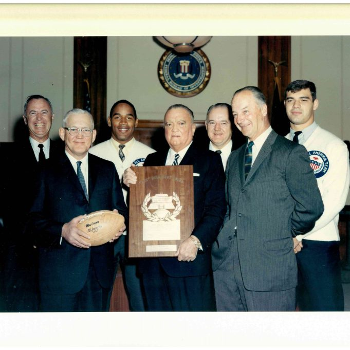 """On December 4, 1967, Honorable Ben Schwartzwalder, Syracuse University, Syracuse, New York, President, The American Football Coaches Association, presented FBI Director J. Edgar Hoover the """"Tuss"""" McLaughry Award at FBI Headquarters, Washington, D.C. Mr. Schwartzwalder was accompanied by Mr. William D. Murray, Durham North Carolina, Executive Director, The American Football Coaches Association; Mr. Gerald B. Zornow, Vice President, Eastman Kodak Company, Rochester, New York,; Mr. Joseph R. Allendorf, Assistant Vice President, Eastman Kodak Company, Rochester, New York; and Mr. O. J. Simpson, University of Southern California, Los Angeles, California, and Mr. Larry Csonka, Syracuse University, Syracuse, New York, members of The American Football Coaches Association All-American Football Team. Shown in Mr. Hoover's Office, left to right, are: Mr. Allendorf, Mr. Schwartzwalder, Mr. Simpson, Mr. Hoover, Mr. Zornow, Mr. Murray, and Mr. Csonka. (Local Identifier: 65-H-2838-02)"""