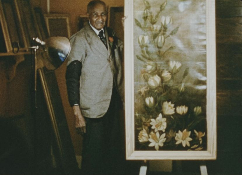 George Washington Carver stands next to one of his paintings in his art studio.