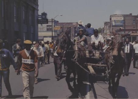 A mule-drawn wagon leads marchers down the streets of Memphis. (Still from 306.6004, reel 6)