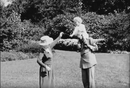 Henry Ford carries his grandson, Henry II, on his shoulders. (Still from FC-FC-4678)