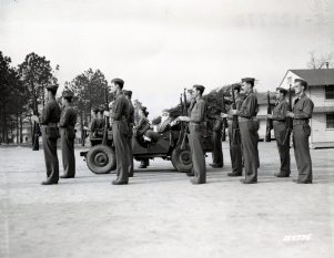 """Photo ID: 111-SC-126776. Original caption: """"Just before Santa Claus leaves his """"jeep-sleigh"""" the guard of honor stands on each side presenting arms to the Christmas visitor. Camp Lee, Virginia, Quartermaster Replacement Center."""" Photo by: Larry Williams. Date: December 1941"""