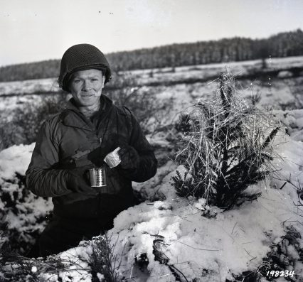 """Photo ID: 111-SC-198234. Original caption: """"S/Sgt. John F. O'Brien of Pittsburgh, Pennsylvania, while in a foxhole, decorates a Christmas tree with C ration can and tinsel dropped from U.S. planes, in the Monschau area, Germany. Tinfoil is dropped by American planes to interrupt the enemy radar system."""" Photographer: Spangle. Date: December 23rd, 1944"""