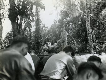 """Photo ID: 127-GW-1083-74820. Original caption: """"It is a Merry Christmas the Marines of the 1st Battalion, 9th Marines have as Chaplain J.A. Rabun leads them in a prayer on Christmas Day. Bougainville."""" Photographer: R. Robbins. Date: December 25th, 1943"""