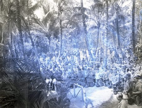 """Photo ID: 127-N-69810. Original caption: """"Christmas Eve on Bougainville was a Holy one. Here, Marines kneel in prayer in a cemetery, where their buddies who fell in combat are buried. Church services are held, following memorial service. In the background, Marines can be seen wondering among the graves, looking for their lost friends."""" Photographer: Kettler. Date: December 24th, 1943"""
