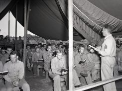 """Photo ID: 127-N-73801. Original caption: """"Christmas morning. MT/Sgt. Frank K. Psaute, Bandmaster (4125 Louisiana St., San Diego, CA), leads singing at Administration Section Chapel. Guadalcanal."""" Photographer: Pfc. C.H. McClure. Date: December 25th, 1943"""