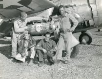 """Photo ID: 342-FH-3A-34904-62668AC. Original caption: """"Banshee pilots with their Christmas present to Hirohito - a gaily decorated bomb attached to the wing of a 10th Air Force fighter plane. Burma."""" Date: December 24th, 1944"""