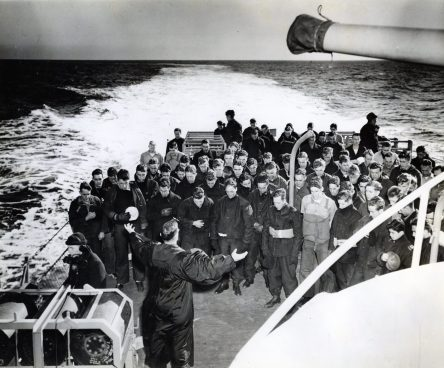 """Photo ID: 80-G-162564. Original caption: """"Enlisted men bow their heads as they follow the prayers of a chaplain on the deck of a warship somewhere at sea on Christmas, 1943. While his shipmates pray, one man on duty (lower left) keeps his ears alert for the orders of war."""" Date: December 25th, 1943"""
