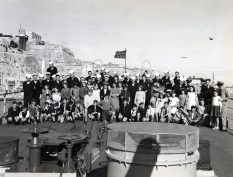 """Photo ID: 80-G-207324. Original caption: """"War orphans of Malta were Christmas dinner guests aboard the USS Brooklyn (CL-40) in Malta Harbor, each with a sailor escort. Later there were gifts and movies in hangar. War orphans and escorts."""" Date: December 25th, 1943"""
