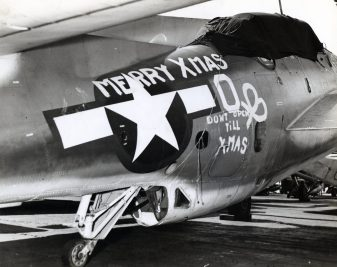 """Photo ID: 80-G-207818. Original caption: """"Merry Christmas!! That's the greeting that Air Group 6, temporarily based aboard the USS Enterprise (CV-6) during recent attacks on the Marshall and Gilbert Islands, sent their mother ship on Christmas Day."""" Date: December 25th, 1943"""
