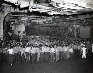 """Photo ID: 80-G-207823. Original caption: """"Following their Christmas Day dinner, officers and crew of USS Enterprise (CV-6) staged an impromptu entertainment on the hangar deck, with everyone invited. Here the Air Officer, Comdr. Thomas J. Hamilton (USN) addresses the spectators and delivers the Yuletide greeting from Capt. Mathias B. Gardner."""" Date: December 25th, 1943"""