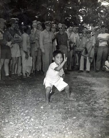 """Photo ID: 80-G-362725. Original caption: """"Natives of Majuro Village Atoll, Marshall Islands, celebrate Christmas. This youthful atoll dweller of Majuro is entertaining his guests with a dance or two. Directly behind the smiling performer is Captain Harold B. Grow (USNR), Atoll Commander of Majuro."""" Photographer: PhoM1/c BR Barrett. Date: December 25th, 1944"""