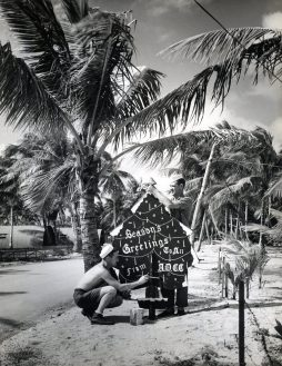 """Photo ID: 80-G-362730. Original caption: """"There wasn't any fragrant pine or mistletoe or drifting snow, but the two blue-jackets pictured here were able to capture the Christmas spirit under the towering palms of this advanced Naval base at Majuro Atoll, Marshall Islands. Standing behind the illuminated Christmas tree is EM3/c Werner Braun (USNR), while kneeling is Rdm2/c Robert Farrell (USNR)."""" Date: December 25th, 1944"""