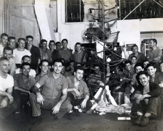 """Photo ID: 80-G-380927. Original caption: """"Christmas night party, decorated tree, and presents aboard the USS Anzio (CVE-57)."""" Date: December 25th, 1944"""