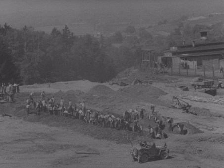 A trench is prepared for a mass grave at Mauthausen. Bodies of those murdered lay in the background.