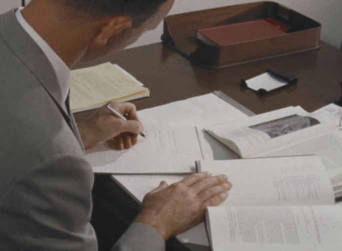 Astronaut Michael Collins sits behind a desk, reading from a book and taking notes.