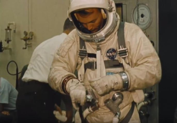 Astronaut Michael Collins adjusts the wrist cuffs on his spacesuit.
