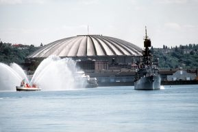 A starboard bow view of the guided missile cruiser USS LEAHY (CG-16), arriving in port during the Seattle Sea Fair 1982. A tug boat sprays water into the air to welcome it. The Kingdome Stadium is visible in the background. Local Identifier: 330-CFD-DN-ST-83-01276 (https://catalog.archives.gov/id/6371846)