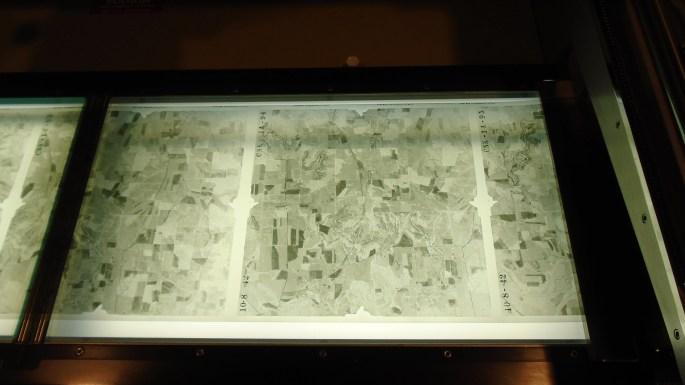 Rolled aerial negatives on light table.JPG