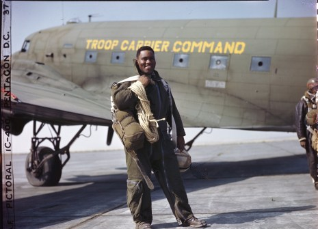342-C-K3746 NAID: 148728164 Original Caption: Operation Firefly - Lt. Clifford Allen of Chicago, Ill. Is one of the fire fighters of the 555th Parachute Infantry Battalion. He wears his complete outfit just before taking off for a jump. Note the 150 ft. rope descending from tall trees; the plastic helmet and catcher's mask are protections against branches and brambles.