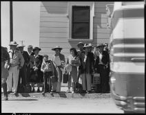 """Original Caption: """"Byron, California. Families of Japanese ancestry, evacuated from Contra Costa County, await bus which will transport them to assembly center at Turlock fairgrounds, 65 miles away. Evacuees will be transferred to War Relocation Authority centers where they will spend the duration."""" Photographer: Dorothea Lange. Date: May 2, 1942. Local ID: 210-G-C101 (NAID 537456)"""