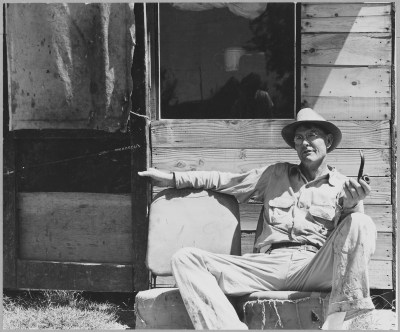 """Original Caption: """"Arvin, Kern County, California. One of a community of shacks in the subdivided orchard rented to agricultural workers on and off relief. Ex-tenant farmer from Oklahoma speaks, """"I was raised in a time when every man hepped himself and the Lord hepped him. Now I haven't made $5 since November 16, 1939. I've raised and matched 6 children back there in Osage County, I had a right smart place, but the land grabbers got me. It's like a man buying a mule, they choose only the best of them. Worlds of them are left out. When I went to farming in 1914 some of them land grabbers was farming with a plow in those days like I was. But a small man can't take the dry weather, the bugs, and all the rest that comes and make it. I stayed together as long as I could. A human being is a funny thing when he knows he's gyped. He wants to take a change somewhere else. I reckon the AAA gyped me out of my share and put me on the road."""" Photographer: Dorothea Lange. Date: April 11, 1940. Local ID: 83-G-41415 (NAID 521659)"""