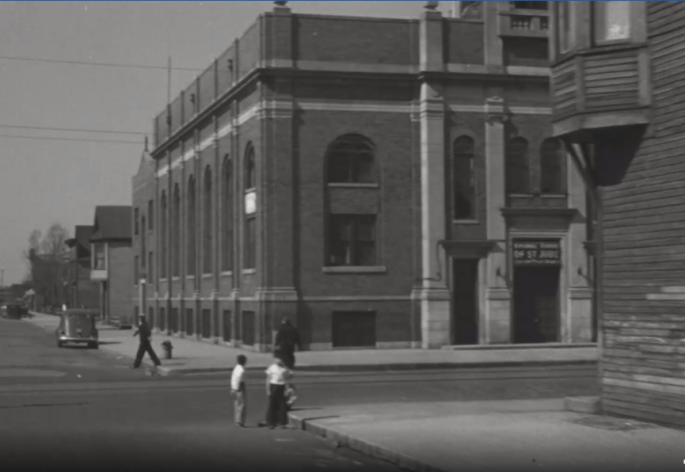 """Front view of a brick church, partially obscured. A sign above the front door reads """"National Shrine of St. Jude."""" Two children play in the street and two adults are walking past the church. A car is parked on the side of the street."""