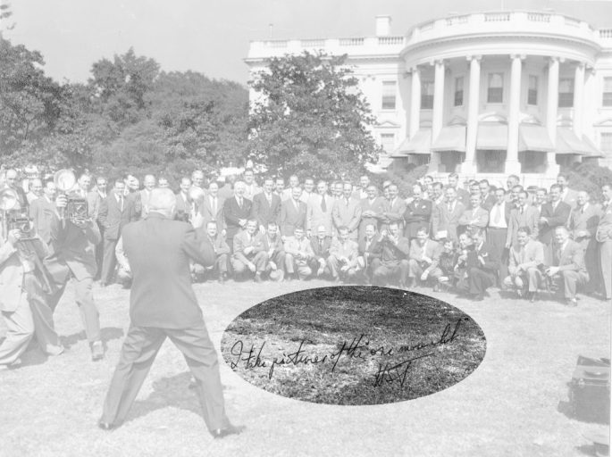 Man with back to camera, takes photograph of a group of men in front of the White House.