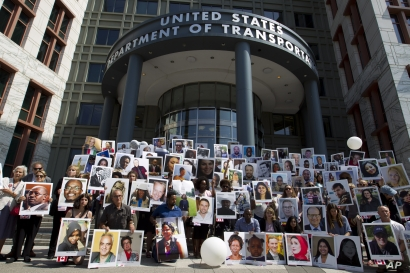 Demonstrators hold pictures of the plane crash victims during a vigil on the six-month anniversary of the crash of a Boeing 737 Max 8, killing 157 people, in Ethiopia on March 10, which has resulted in the grounding hundreds of the planes worldwide,…