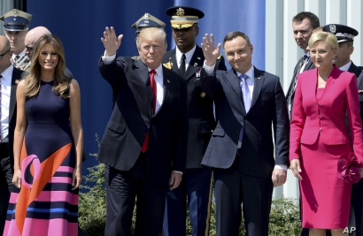 U.S. President Donald Trump, left, waves along with Poland's President Andrzej Duda, as U.S. First Lady Melania Trump, left and Poland's first lady Agata Kornhauser-Duda, right, stand by, in Krasinski Square, in Warsaw, Poland, July 6, 2017.