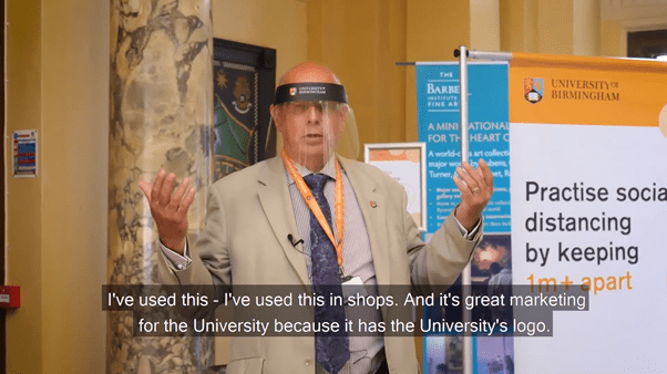 """University of Birmingham VC wearing branded face visor. Subtitle reads """"I've used this - I've used this in shops. And it's great marketing for the University because it has the University's logo."""