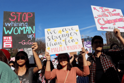 Supporters of the Women's March hold up their creative and artistic signs.