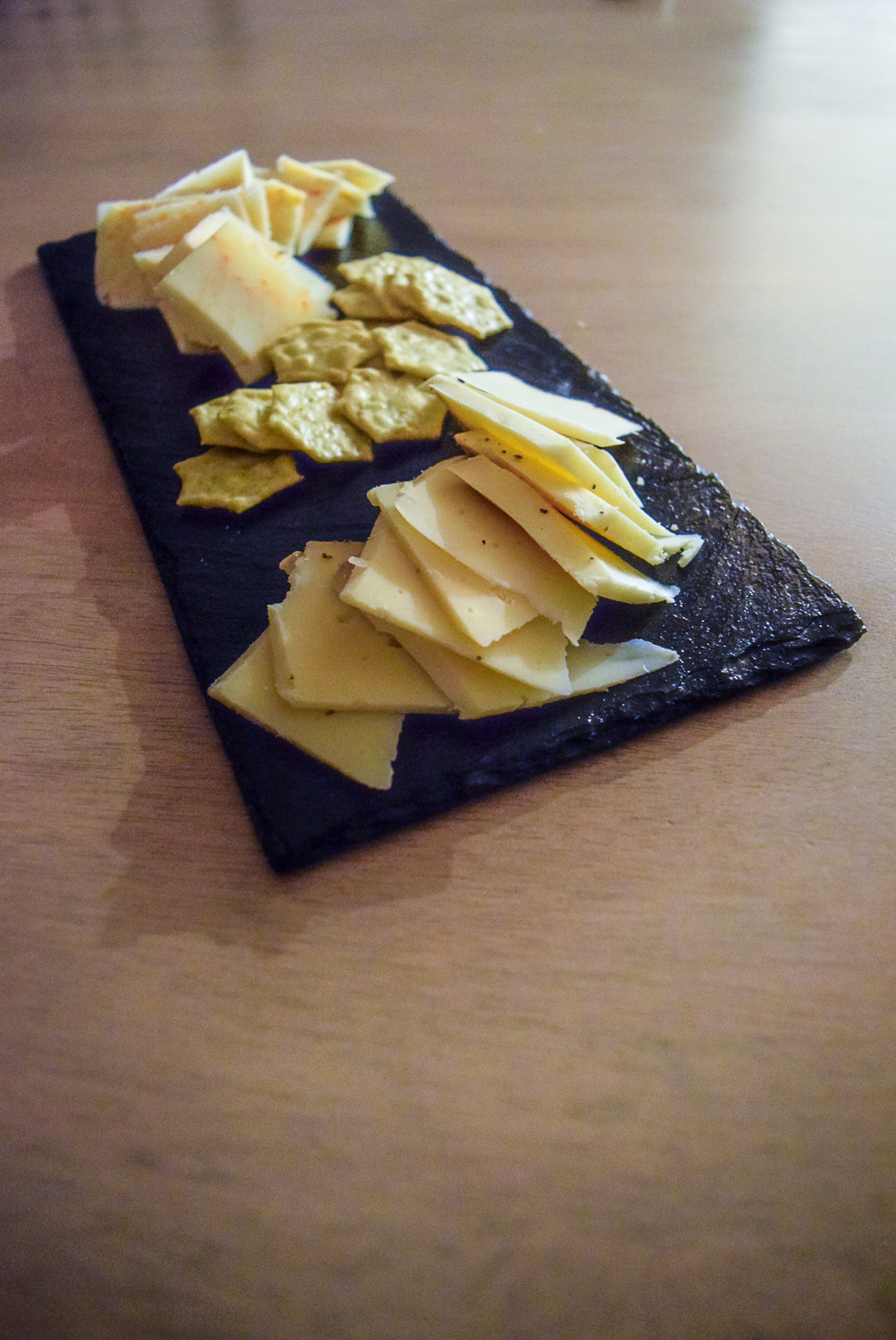Front view of Gluten-Free Peppery Slate Cheeseboard with Trader Joe's Gluten-Free Savory Thin Mini Edamame Crackers