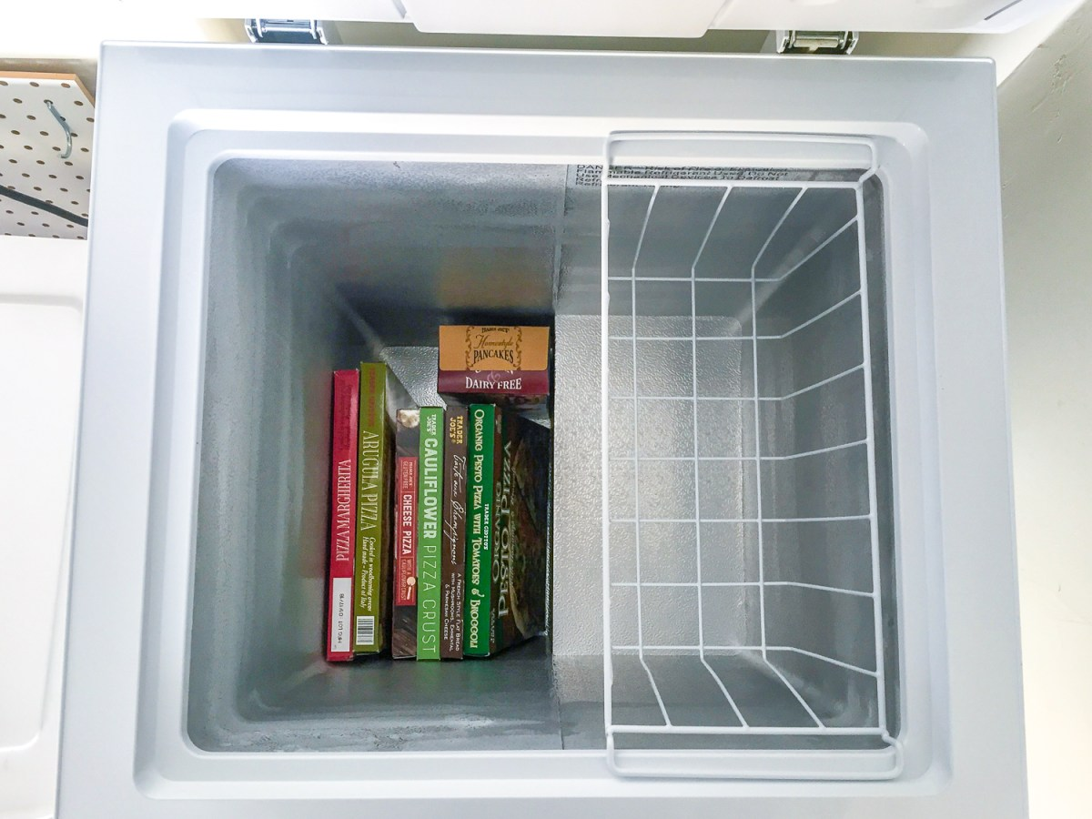 Top view of open inside of Insignia 3.5 Cu. Ft. Chest Freezer filled with Trader Joe's frozen pizzas